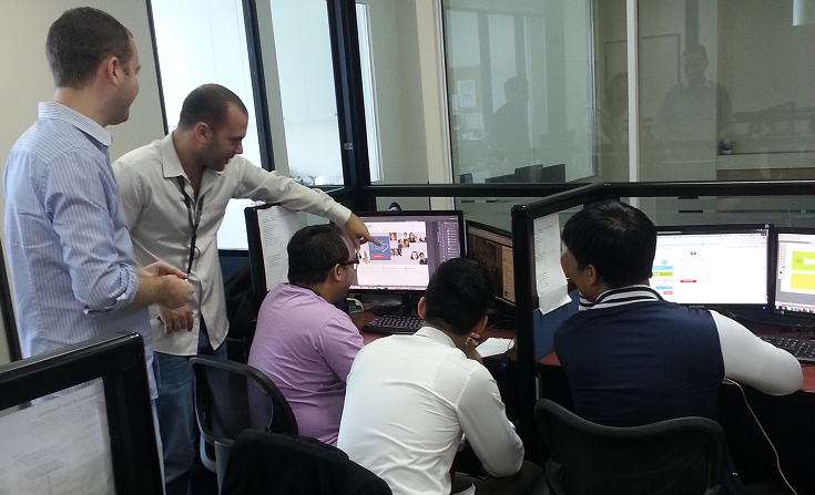 The TrueLogic sales and marketing director, CEO, and team members working on a web design project together