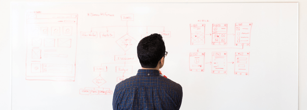 Man looking at a whiteboard with processes and data